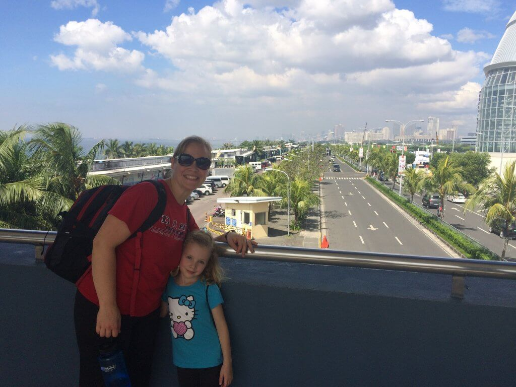woman and girl on overpass over road