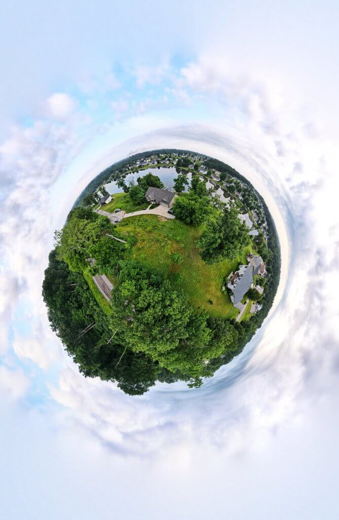 drone 360 degree picture of trees, houses, and lake