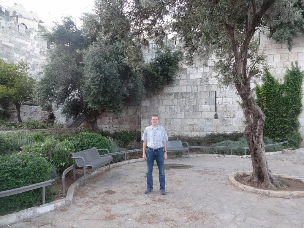 man in front of stone wall with green trees and bushes