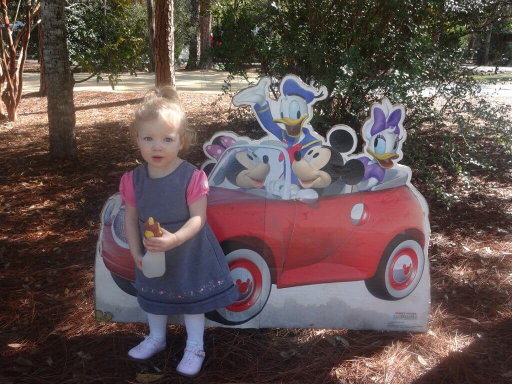 girl in a dress in front of Mickey Mouse sign