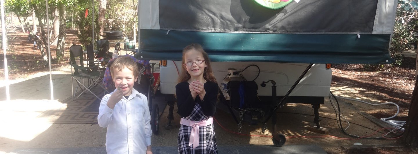 boy and girl holding lizards in front of camper trailer