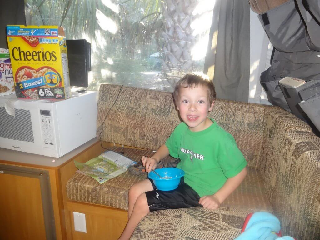 boy eating from a blue bowl on a couch