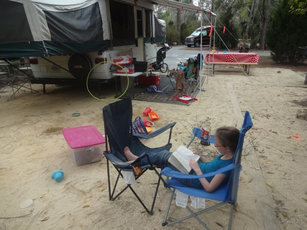 girl reading on a camp chair with pop-up trailer