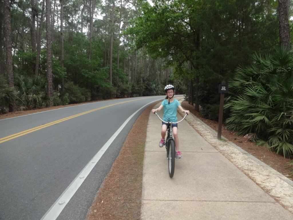 girl on a bike on sidewalk