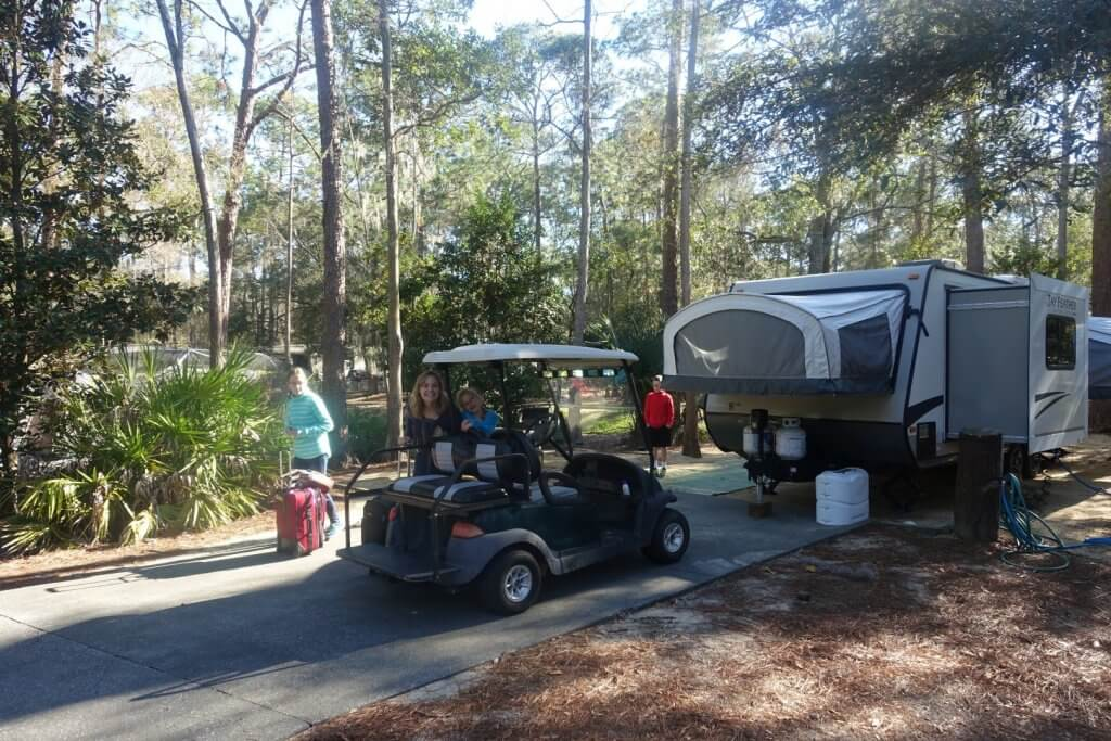 mother and kids with golf cart and pop-up trailer at campsite
