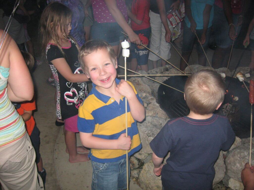 boy with marshmallows on a stick at campfire with others around