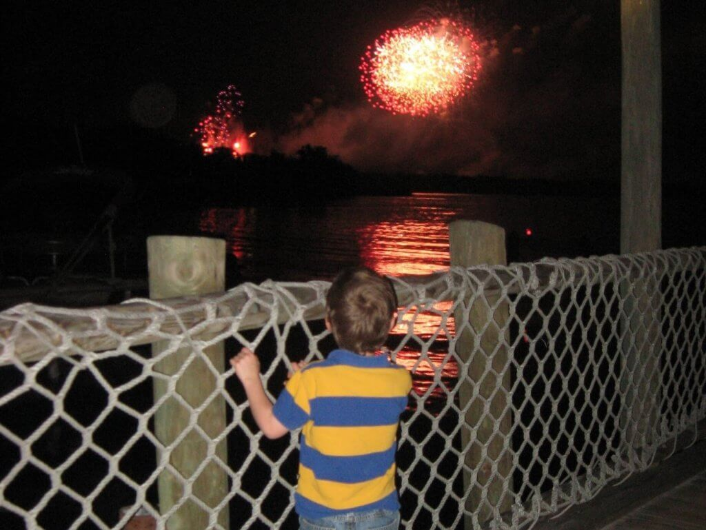 boy at a fence watching fireworks over water