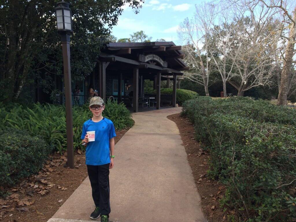 boy with cup on sidewalk