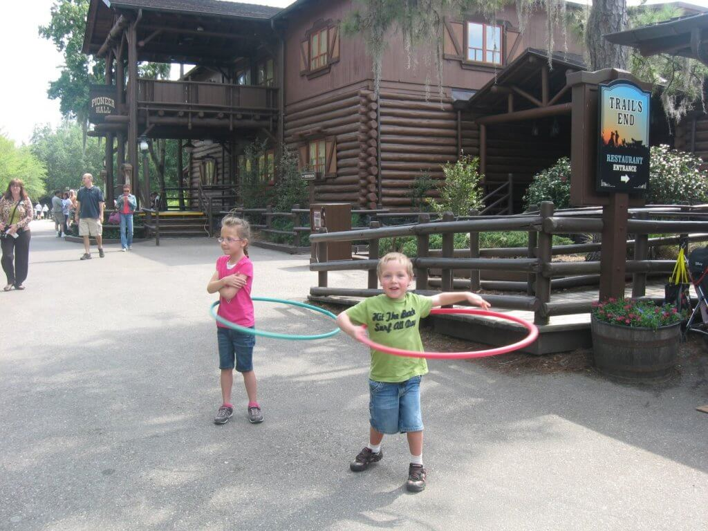 kids playing with hoola hoops in front of log building