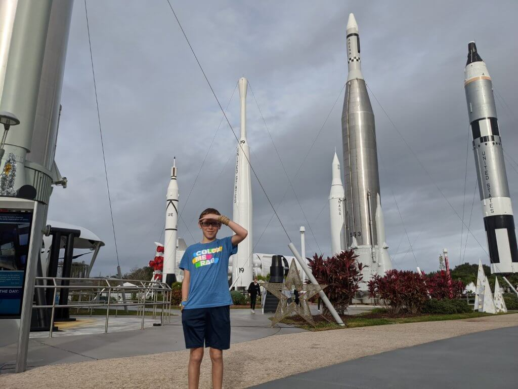 boy in front of several rockets