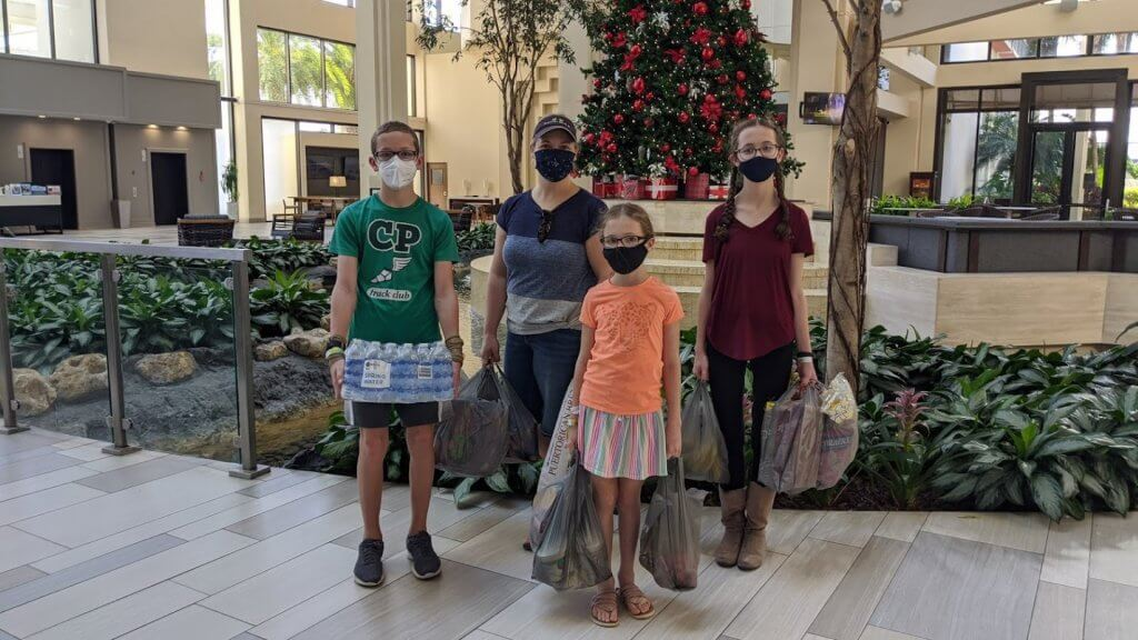 family with masks and grocery bags