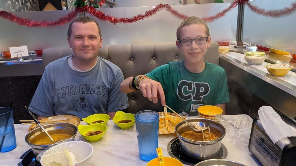 father and son eating at restaurant