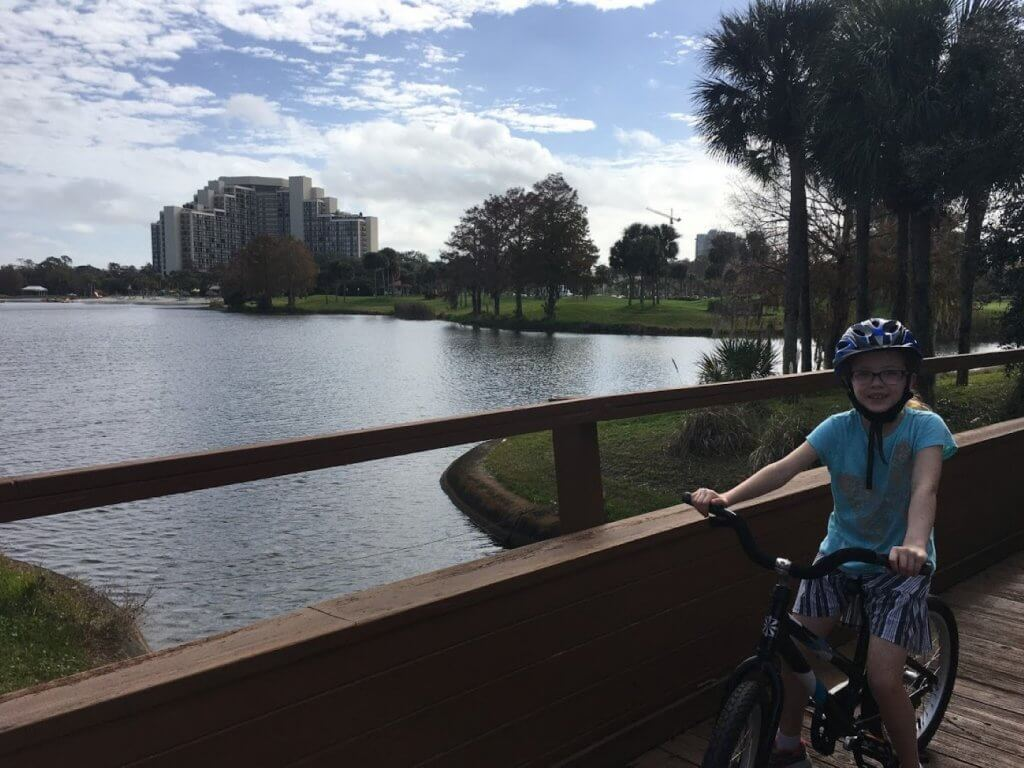 girl on bike in front of pond